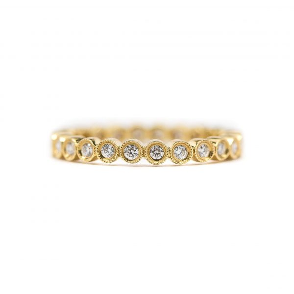 , 18kt yellow gold; stones vary in size; bezel set diamond eternity band with milgrain edges